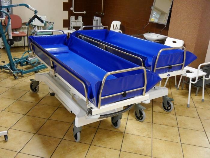 Wózek transportowo-kąpielowy posiadający wanną z PCV, obudowę ramy dolnej, koło kierunkowe, nierdzewne barierki.